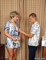 A short-haired mature blond in a bleu gown performs blowjob for a youngster